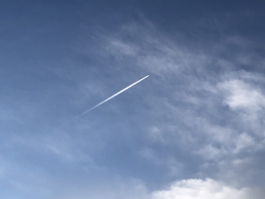 A plane soars through the air leaving a streak of clouds behind.