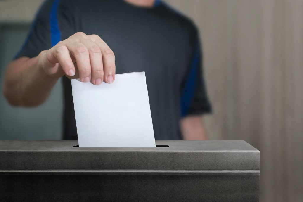 hand putting blank ballot into ballot box
