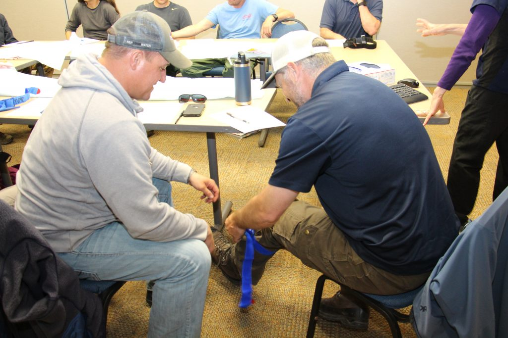 Michael St. Martin (left) and Lance Broyles (right) practice applying a tourniquet during Stop the Bleed training with fellow US Forest Service staff on Monday, May 6, at UCHealth Yampa Valley Medical Center.