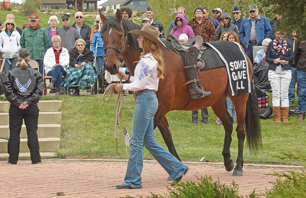 Hallie Myhre leads Kermit during the Memorial Day Ceremonies at the Steamboat Springs Cemetery Monday. The rider less horse is a traditional way to honor those that have been killed serving their country.