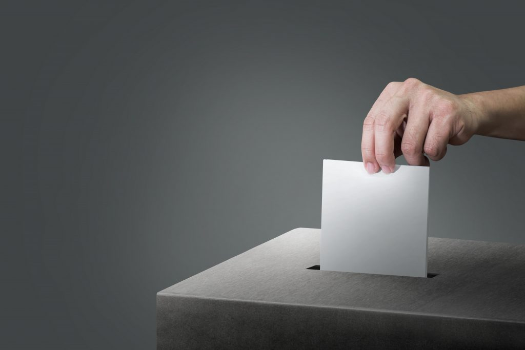 A hand places a ballot in a box.