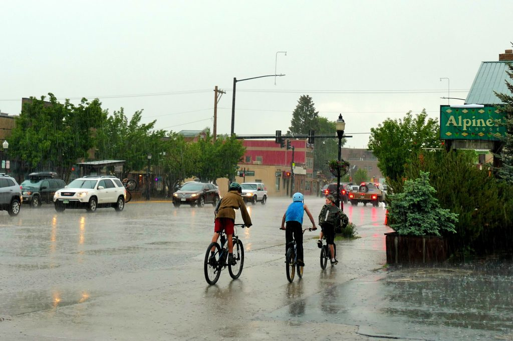 Three boys get caught in a downpour while riding their bikes.