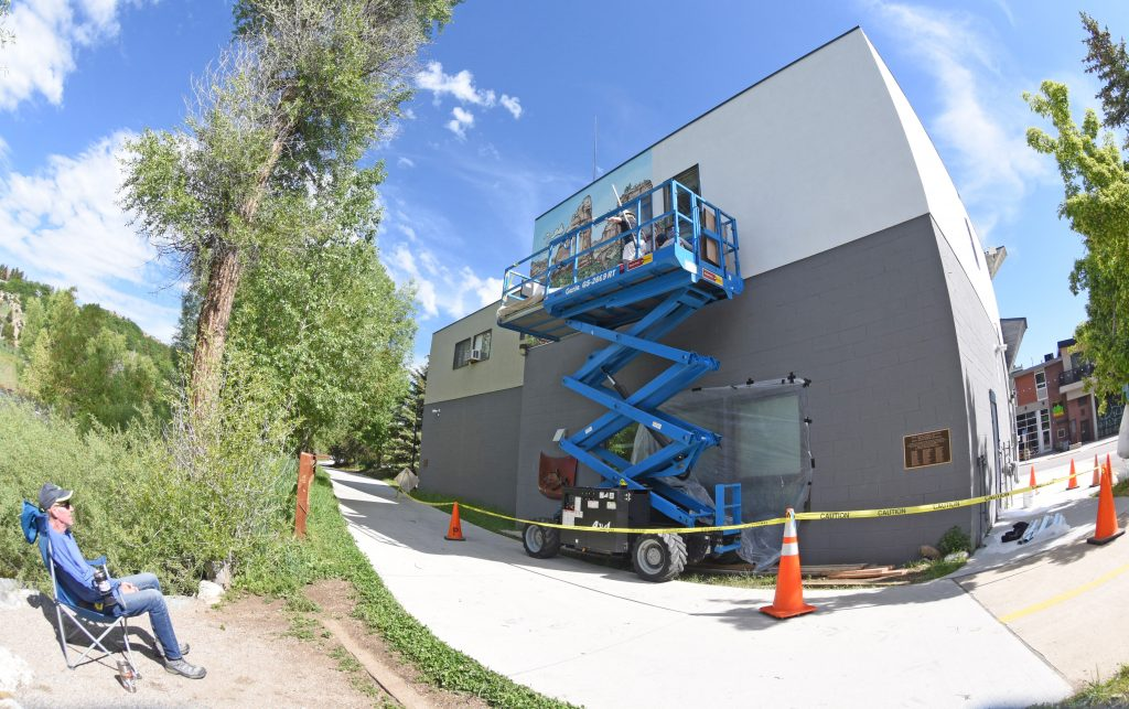 Jack Legrice sits back and watches as workers install a new mural on the back of the Routt County Search and Rescue Barn in downtown Steamboat Springs. When fully installed, the mural, which traces the Yampa River's journey from the head waters in Flat Tops Wilderness Area to its confluence with the Green River in Dinosaur National Park, will stretch 70 feet across two sides of the building.