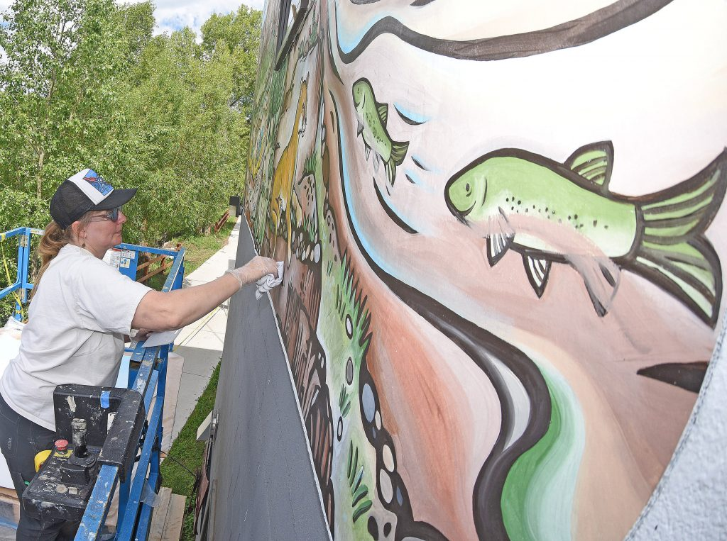 Jill Bergman cleans up one of the many vinyl panels that are being used to complete a new mural, that when finished, will stretch across the top of the Steamboat Search and Rescue Barn located along the Yampa River Core Trail in downtown Steamboat Springs.
