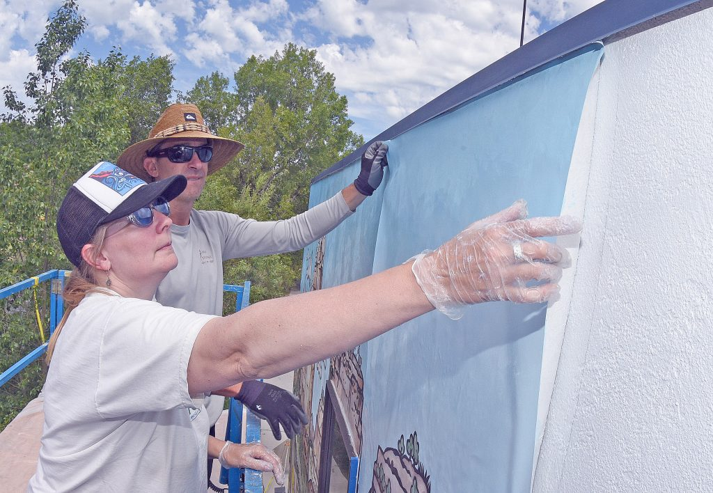 Artist Jill Bergman and Kent Vertrees, with Friends of the Yampa, install a vinyl panel for a new mural on the top level of the Steamboat Search and Rescue in downtown Steamboat Springs.