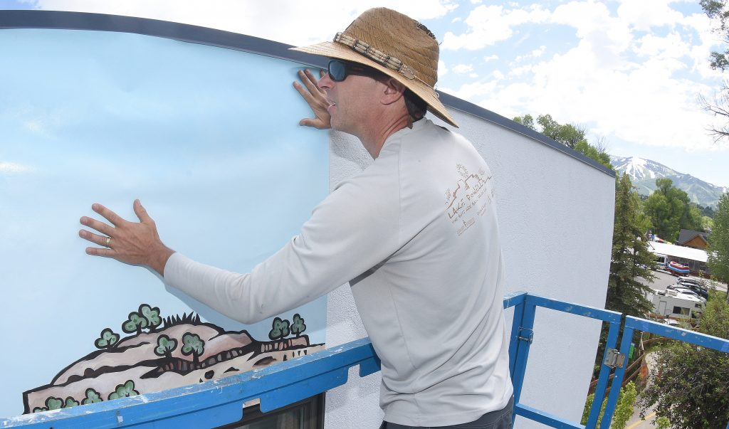 Volunteer Kent Vertrees, who is with Friends of the Yampa, straightens one of the many panels that will form a new mural on the top level of the Routt County Search and Rescue Barn.