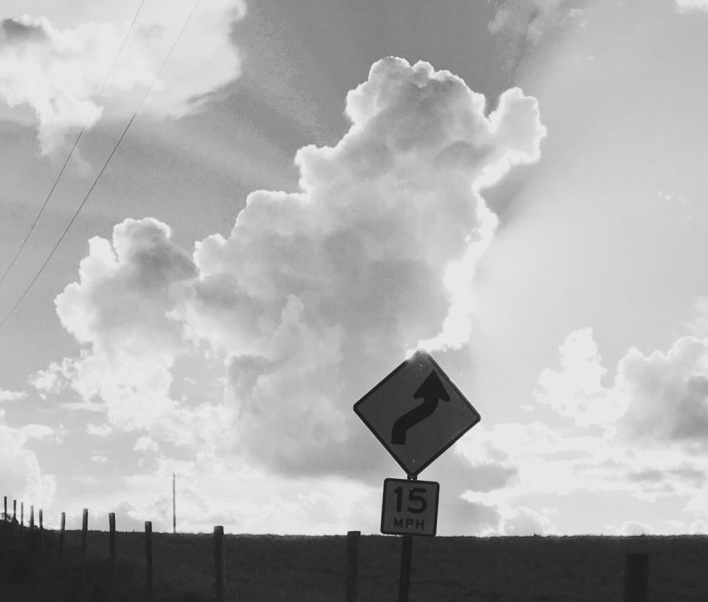 A cloud moves perfectly atop a winding road sign.