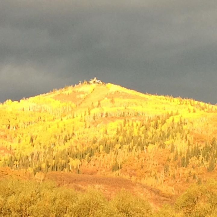The sun setting on Mount Werner turns the fall colors gold.