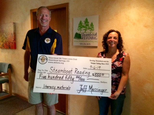 The Ski Town Lions Club proudly present a check to Kim Schulz with Steamboat Reading. The funds will be used for literacy materials.