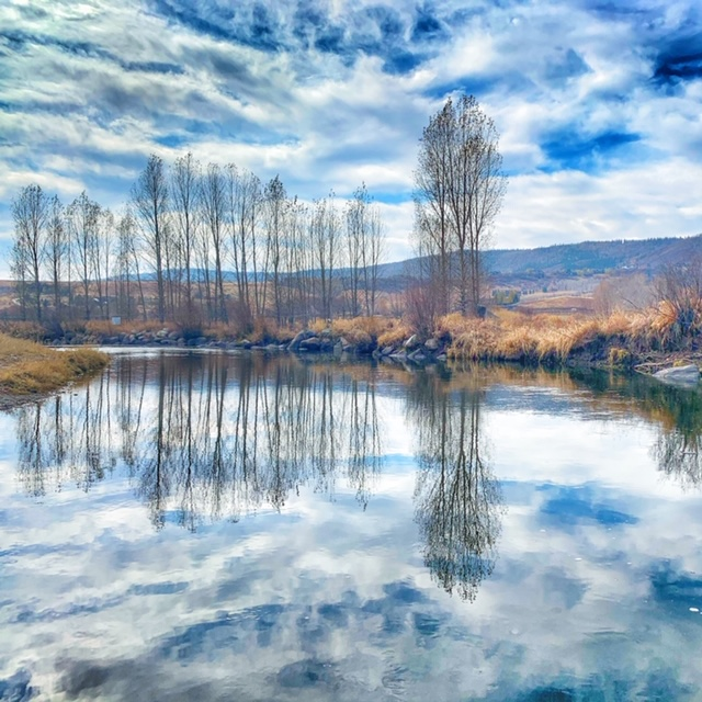 The Yampa River reflects the trees like glass.