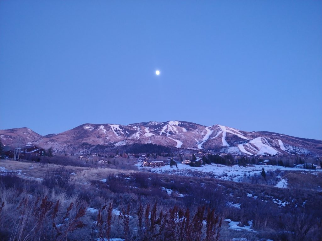 The moon rises over Steamboat Springs as dusk settles in.