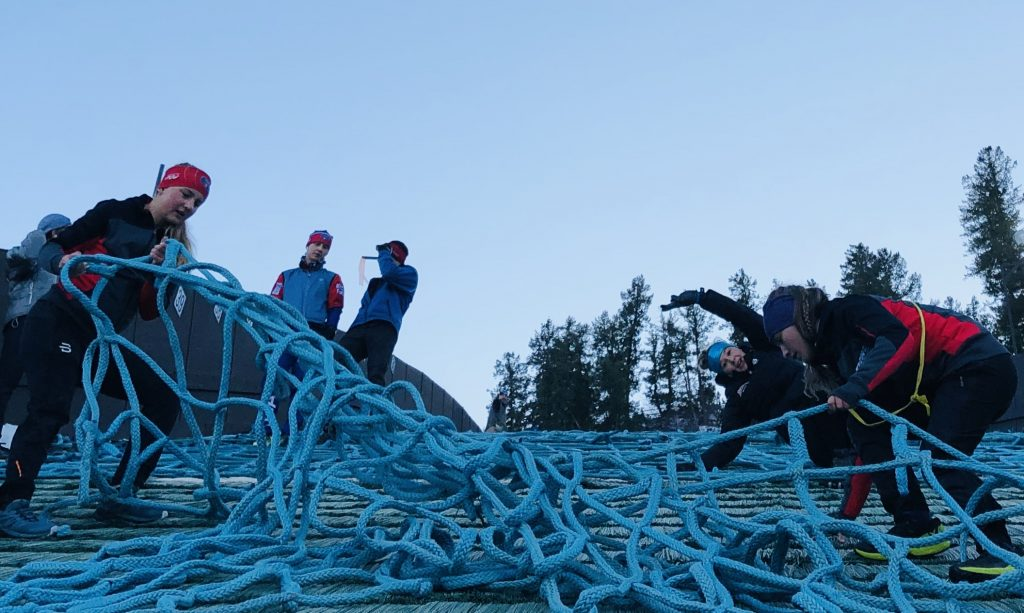 Spider-(wo)men in training. Teamwork to get snow nets on the jumping hill so these kids can fly again.
