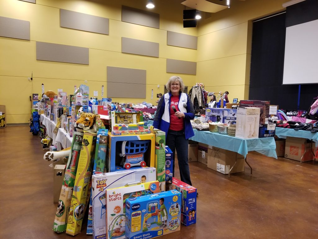 Kate Nowak, the Routt County United Way executive director, poses near gifts for the Holiday Gift Exchange in Steamboat Springs.