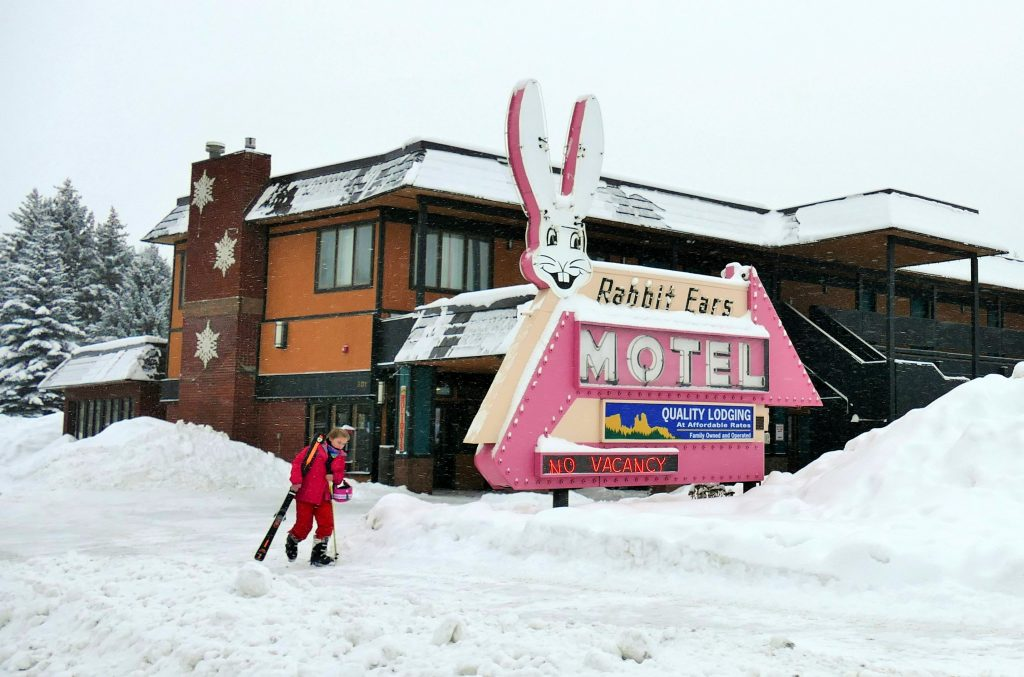 This picture is of a young skier walking to the bus stop in front of the historic Rabbit Ears Motel sign. Notice the No Vacancy sign. Town is full of happy skiers and riders right now, so they're all enjoying the fresh powder up on the mountain.