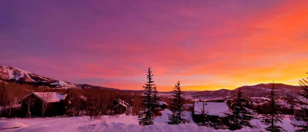 The sun sets over Steamboat Springs, painting the sky pink and orange.