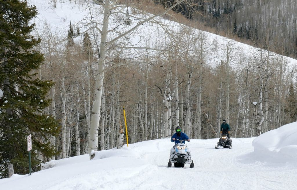 "Here are three pictures of snowmobilers on Buffalo Pass (called ""Buff Pass"" by the locals) today, in Routt County (Steamboat Springs). The sign says Road Closed but Snowmobiles and Snowcats are excepted)."