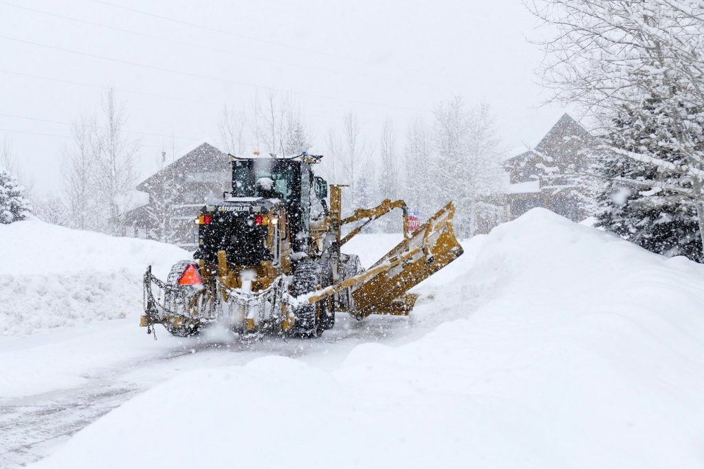 A snowplow works to clean streets as snow continues to fall Thursday, Feb. 6.