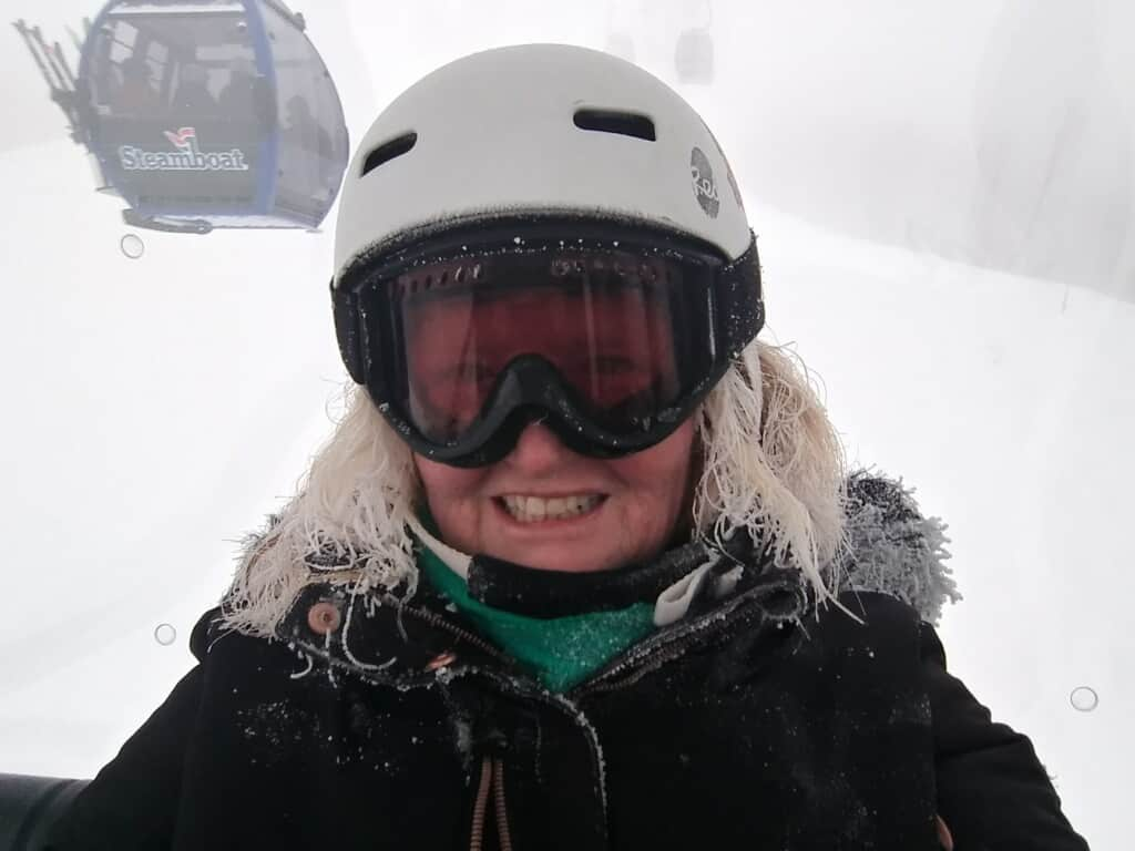A skier smiles as snow pounds down at Steamboat Resort.