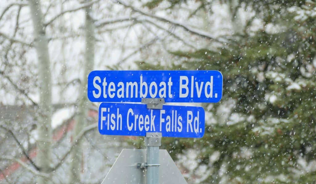 a snowy street sign for Steamboat Blvd., with a Fish Creek Falls Road sign