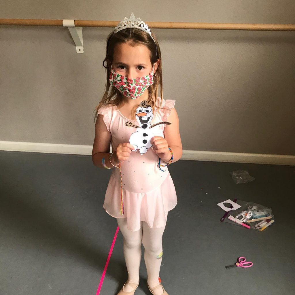 A young dancer shows off her artwork during summer dance camp.