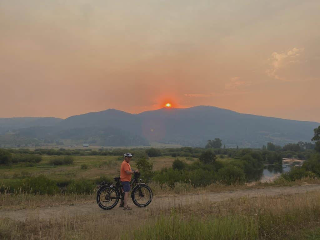 Sam Sullivan bikes along the Yampa River just before the sunset on Emerald Mountain on Tuesday evening through both haz & smoke. Incredibly beautiful for such a disaster going on elsewhere!!